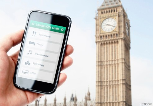Hand holding smartphone with city guide in London